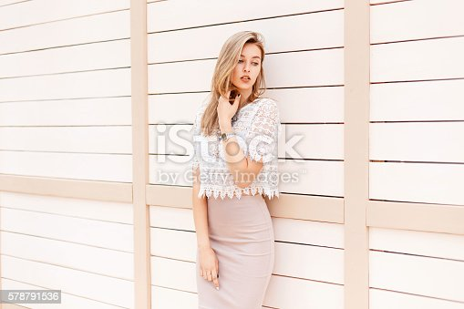 578791454istockphoto Beautiful woman in summer shirt with vintage lace near wall 578791536