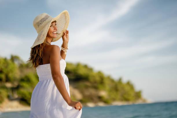 plajda yaz günü zevk sundress güzel kadın. - beyaz elbise stok fotoğraflar ve resimler