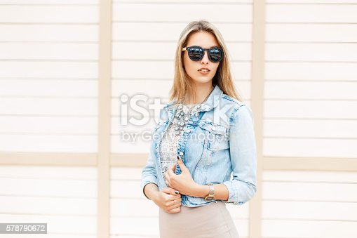 578791454istockphoto Beautiful woman in sunglasses and jeans jacket near wooden wall 578790672