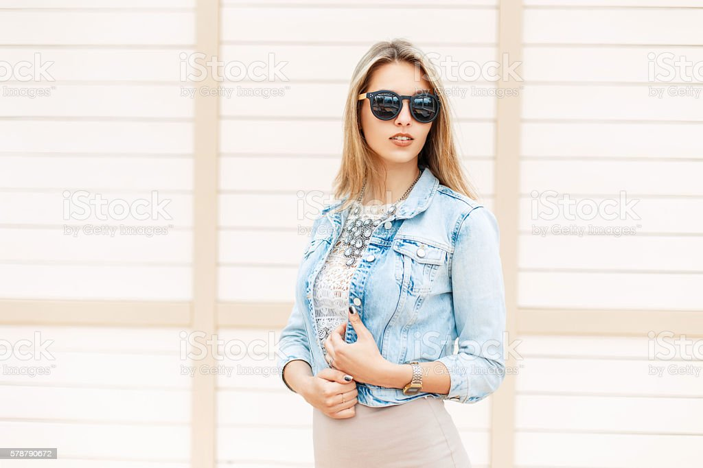 Beautiful woman in sunglasses and jeans jacket near wooden wall stock photo