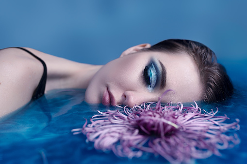 istock Beautiful woman in the bath with flowers. Rejuvenation concept 1199838706