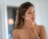 Portrait of a beautiful woman in the bathroom applying cream on her face and looking in the mirror