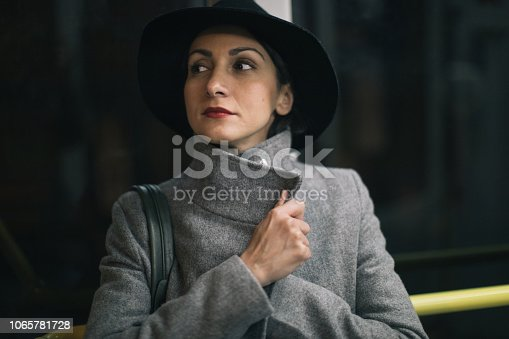Young beauty woman with hat driving at night in the bus, standing