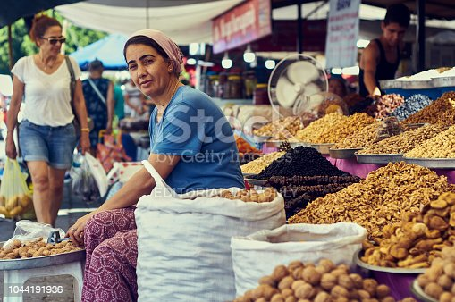 A beautiful woman in traditional clothes sells nuts and oriental sweets in the market in Turkey. The city of Turgutreis , Bodrum - 2018. The coast of the Aegean Sea.