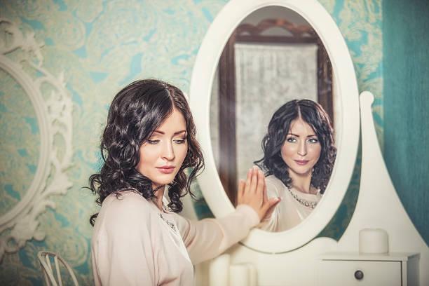 Belle femme dans le miroir reflétait le sourire magiques - Photo