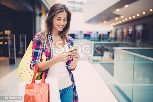 Smiling woman with shopping bags in the clothing store texting on smartphone