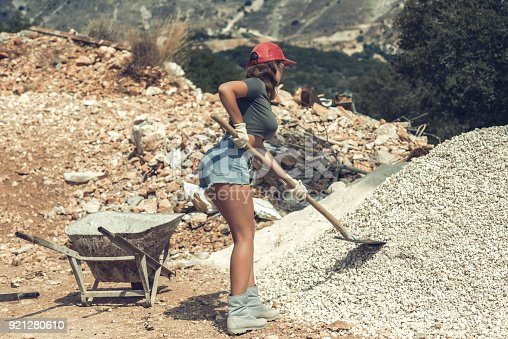istock Beautiful woman in the shorts and in the red peaked cap with a wheelbarrow for cement on a construction site 921280610
