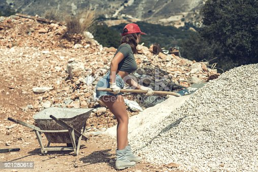 istock Beautiful woman in the shorts and in the red peaked cap with a wheelbarrow for cement on a construction site 921280616