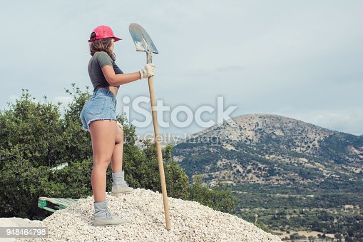 istock Beautiful woman in the shorts and in the red peaked cap with a wheelbarrow for cement on a construction site 948464798