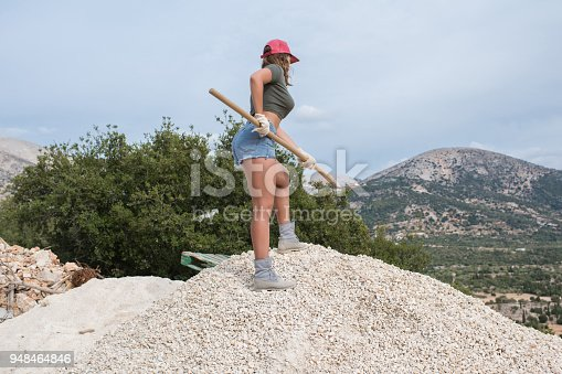 istock Beautiful woman in the shorts and in the red peaked cap with a wheelbarrow for cement on a construction site 948464846