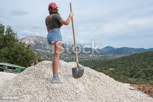 istock Beautiful woman in the shorts and in the red peaked cap with a wheelbarrow for cement on a construction site 948464882