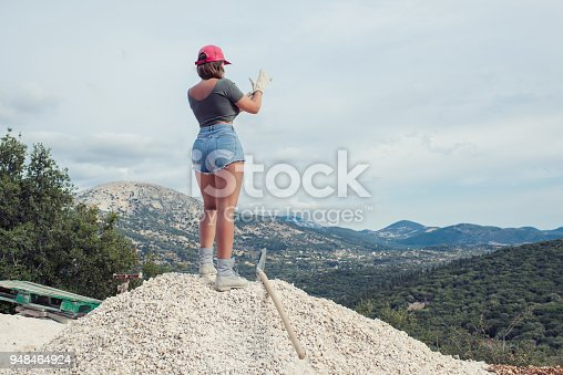 istock Beautiful woman in the shorts and in the red peaked cap with a wheelbarrow for cement on a construction site 948464924
