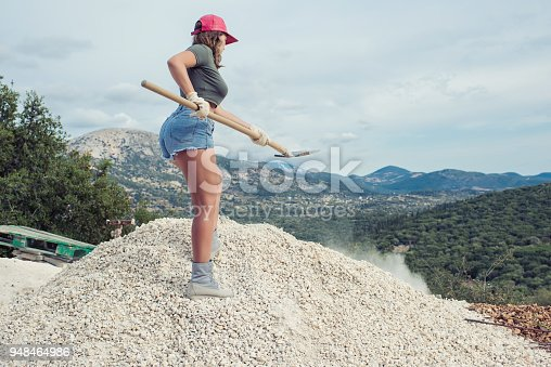 istock Beautiful woman in the shorts and in the red peaked cap with a wheelbarrow for cement on a construction site 948464986
