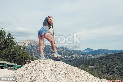 istock Beautiful woman in the shorts and in the red peaked cap with a wheelbarrow for cement on a construction site 948464990