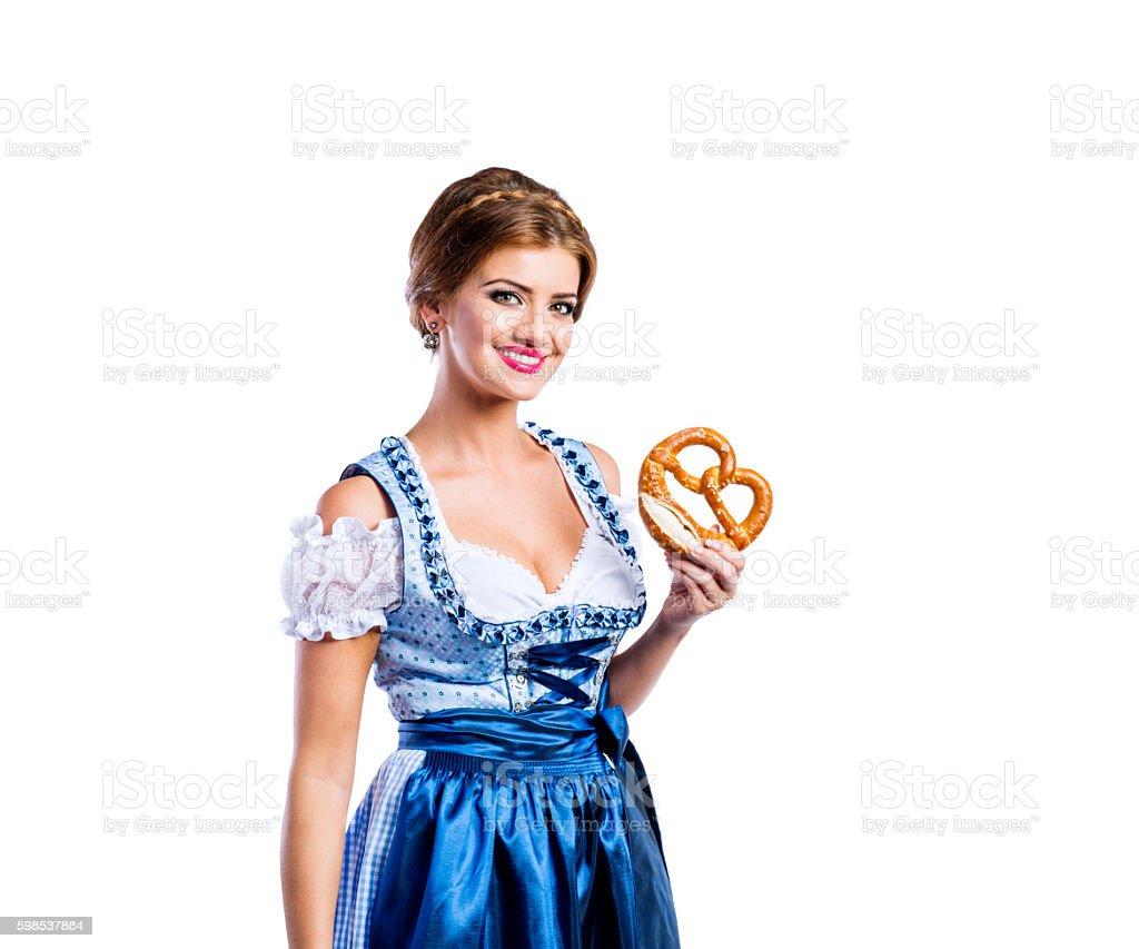 Beautiful woman in traditional bavarian dress holding a pretzel photo libre de droits