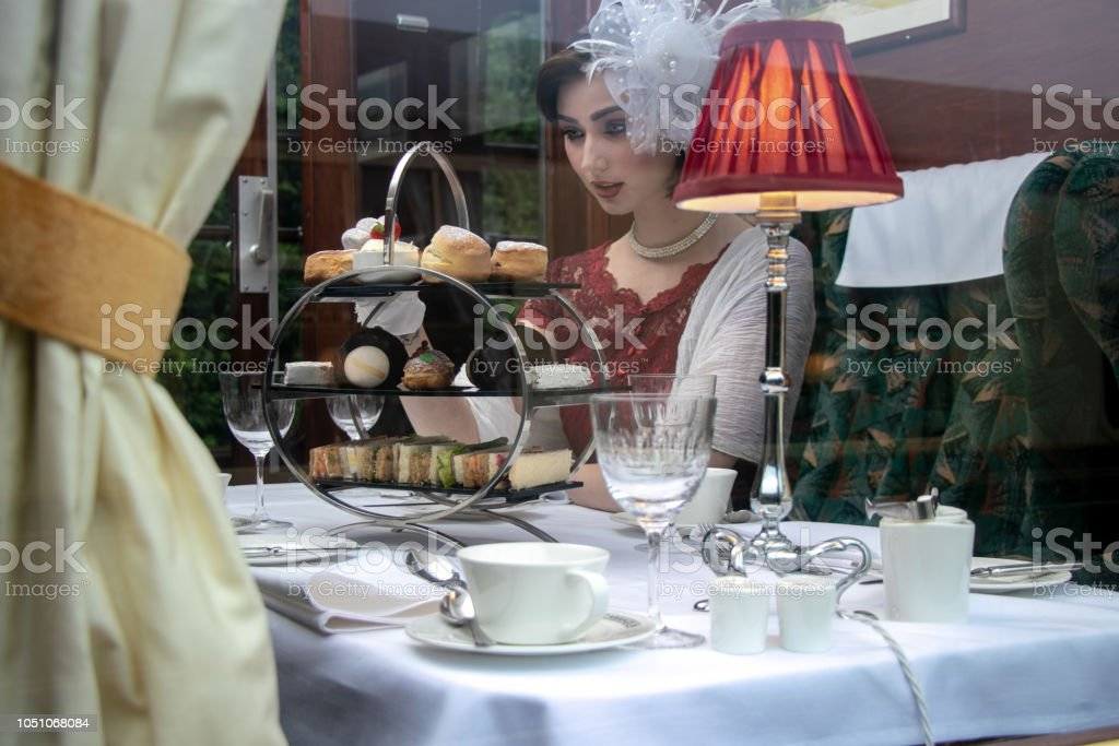 Beautiful woman in vintage clothing enjoying afternoon tea in train carriage stock photo