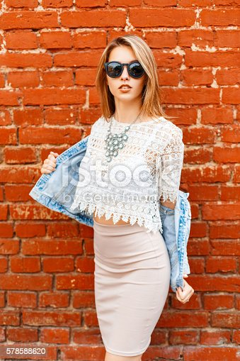 578791454istockphoto Beautiful woman in vintage lace blouse and sunglasses, jeans jacket. 578588620