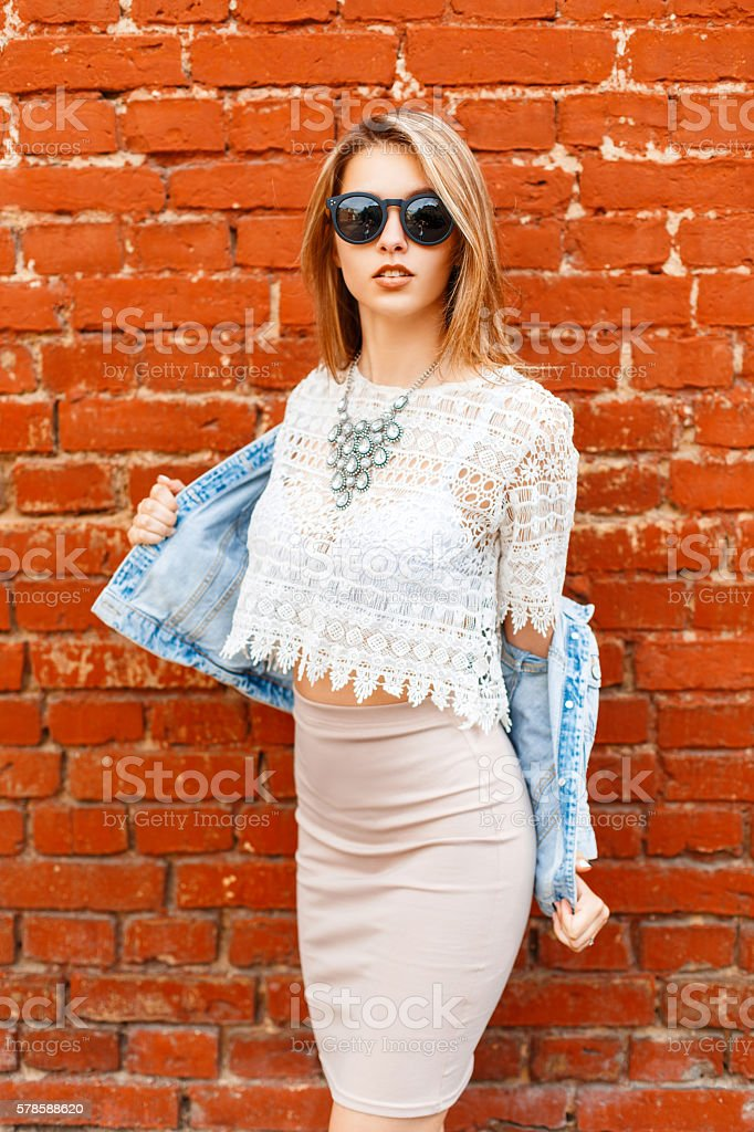 Beautiful woman in vintage lace blouse and sunglasses, jeans jacket. stock photo