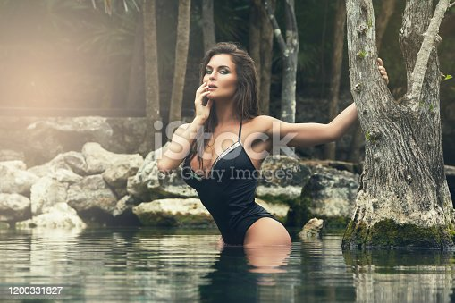 istock Beautiful woman in water 1200331827