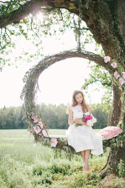 Beautiful woman in white dress on swing outdoors with flowers – Foto