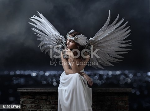 Young woman with angel wings on a background of night city
