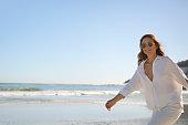 istock Beautiful woman in white running on the beach 1267095813
