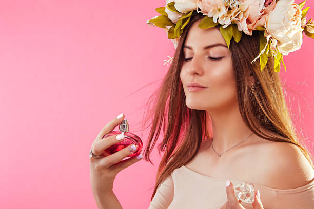 Mulher bonita em grinalda aplicar perfume - foto de acervo