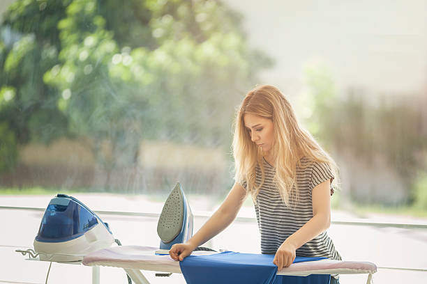 beautiful woman ironing some clothes - ironing stock photos and pictures