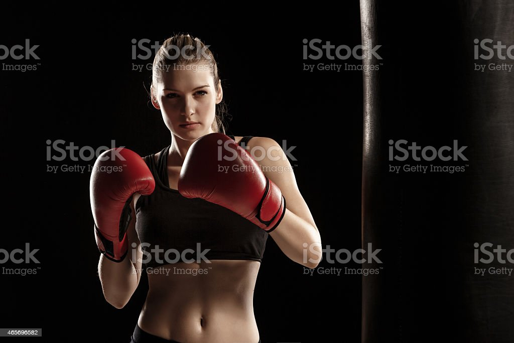 beautiful woman is boxing on black background stock photo