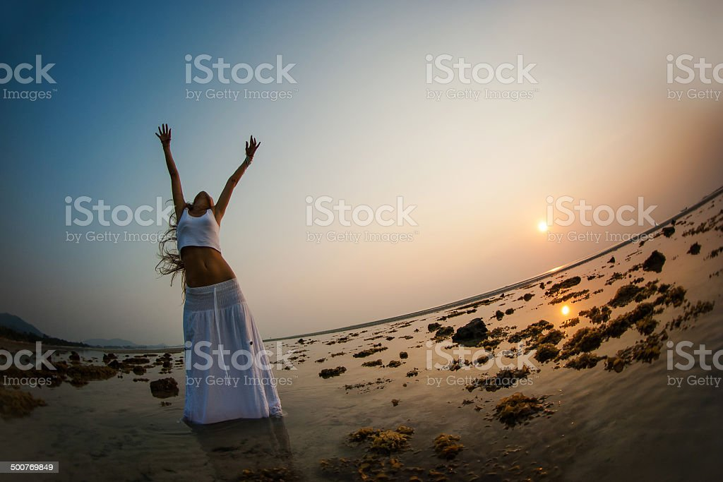 Beautiful woman is dancing on the beach at sunset stock photo