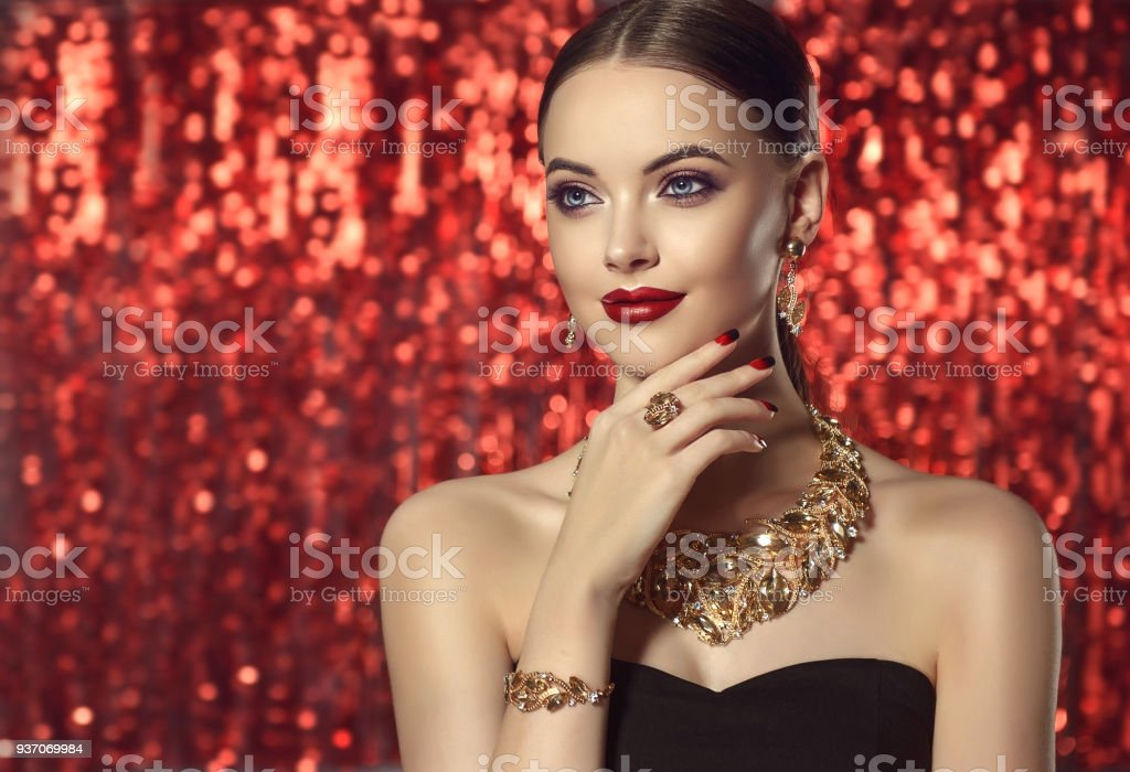 Beautiful woman is demonstrating gilded jewelry set and perfect makeup. - Foto stock royalty-free di Accessorio personale