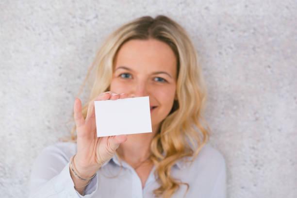 Schöne Frau hält weiße Karte für Kopierplatz – Foto