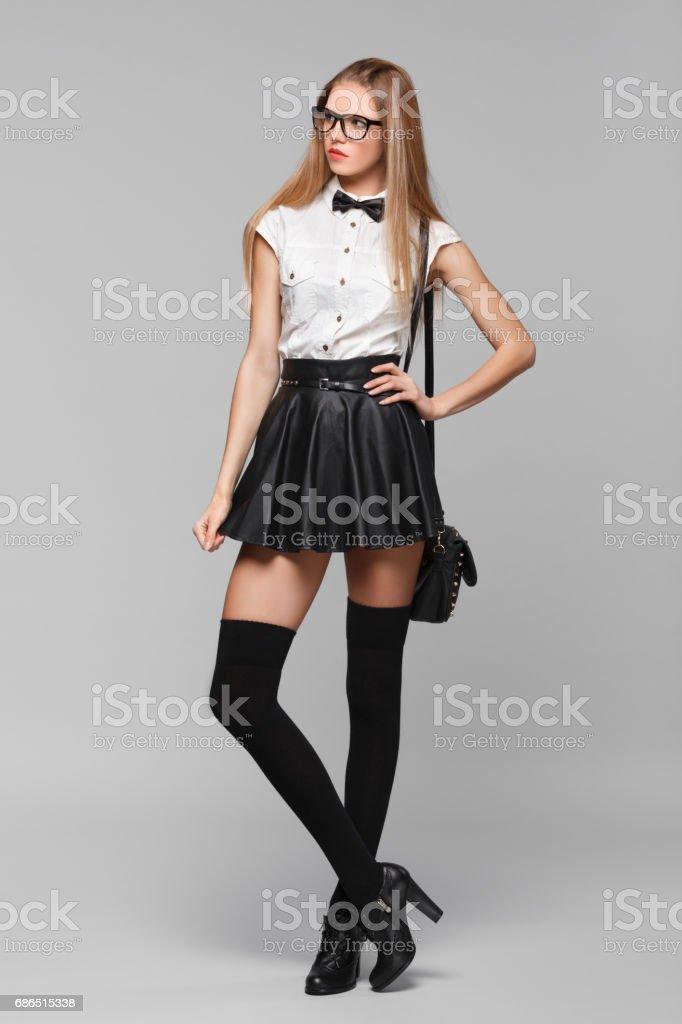 Beautiful woman is in fashion style in black mini skirt. Fashion girl stock photo