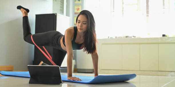 A beautiful woman is looking into a computer tablet while doing an exercise in a comfortable living room. stock photo