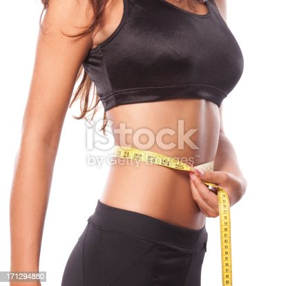 A beautiful tanned and fit woman is measuring her waist.