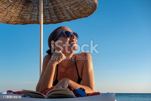 Beautiful woman is reading book on the sunbed on the beach