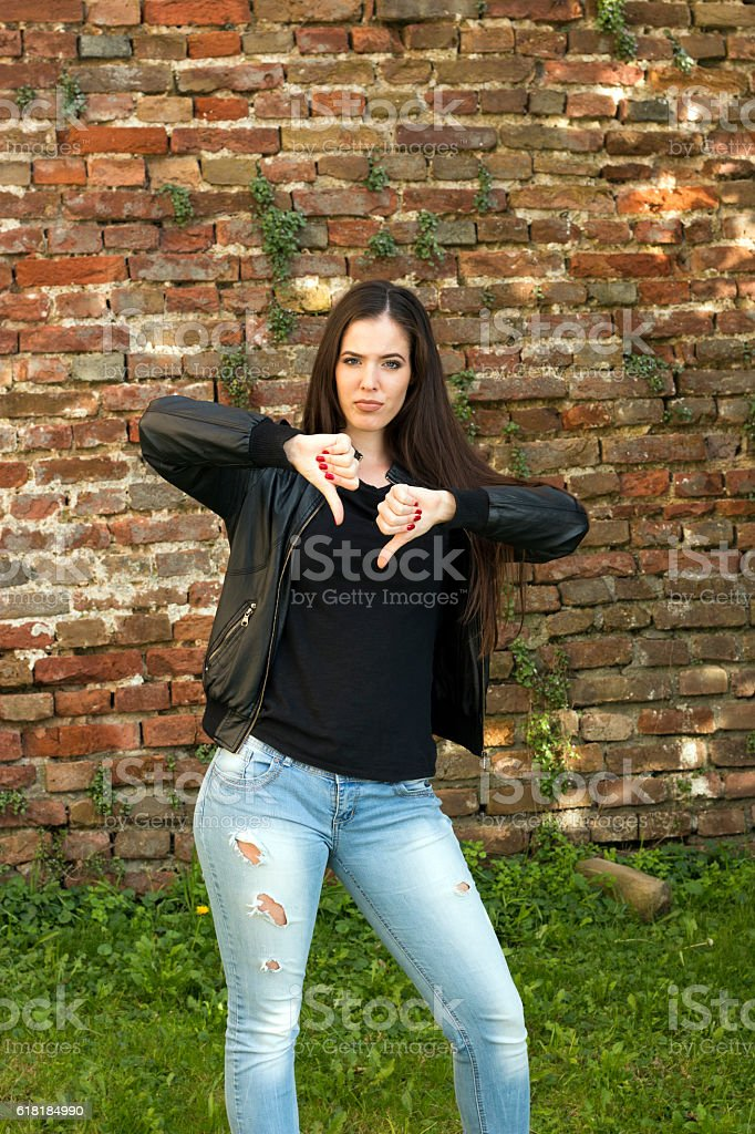 Beautiful woman is standing and shows thumbs down stock photo