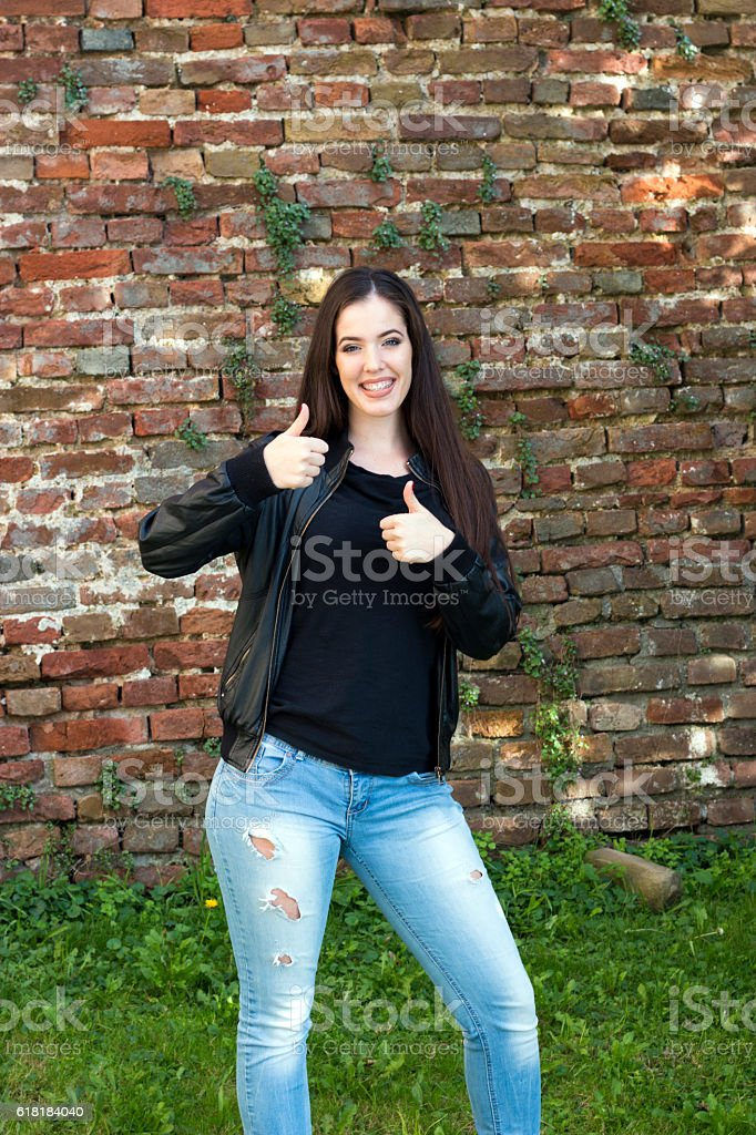 Beautiful woman is standing and shows thumbs up stock photo
