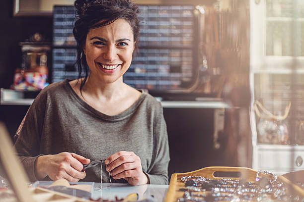 Beautiful woman jewelry maker Jewelry maker woman in her store. craftsperson stock pictures, royalty-free photos & images