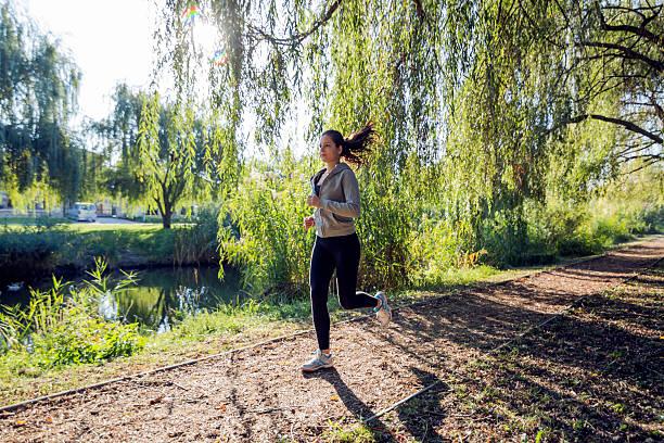 schöne frau joggen in der natur - joggerin stock-fotos und bilder