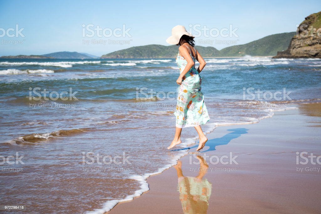 Beautiful woman jumping a small wave of the sea, happily, in a flowery dress and hat, on a sunny day. stock photo