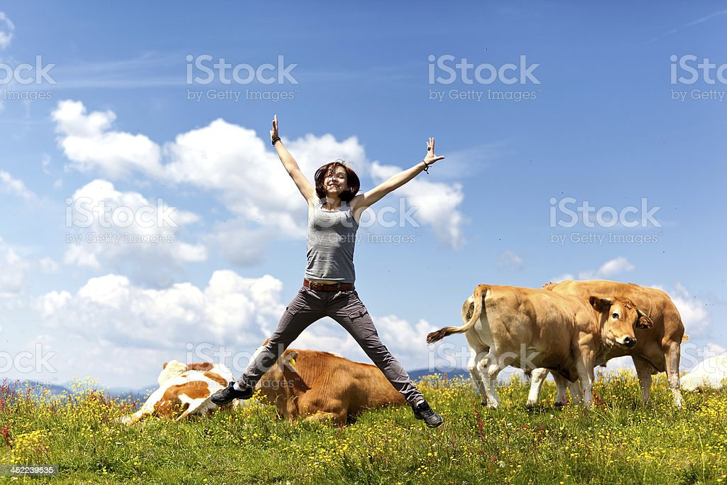 beautiful woman jumping between cattle herd royalty-free stock photo