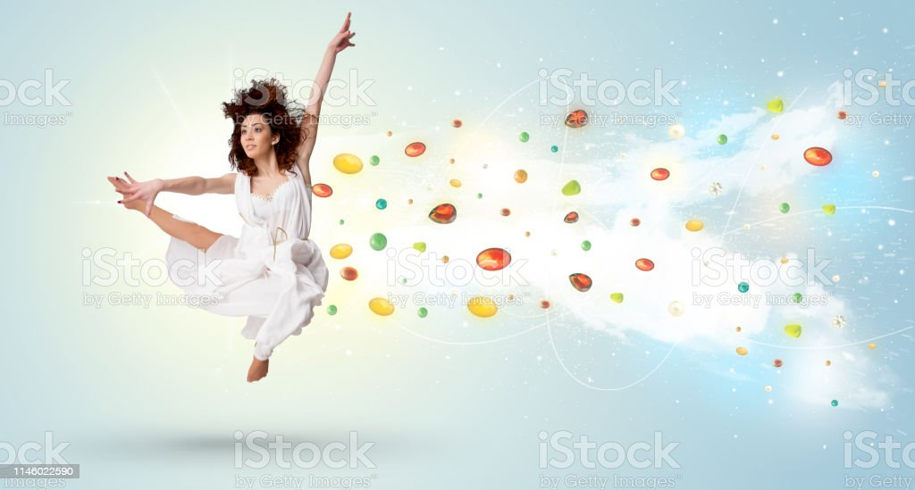 Beautiful woman jumping with colorful gems and crystals on the...