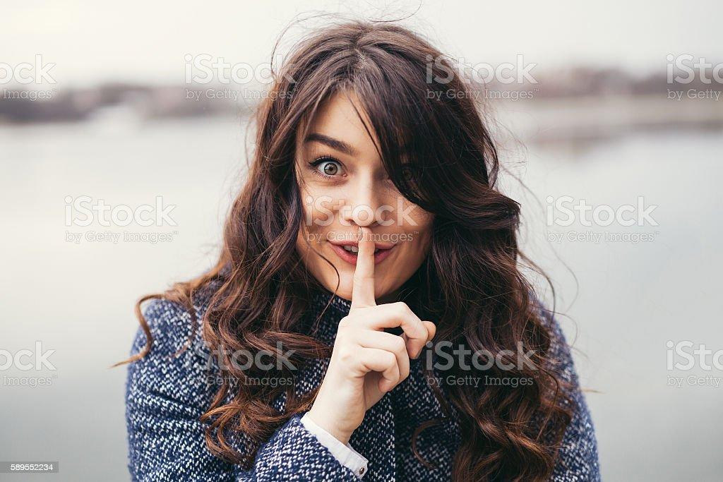 Beautiful woman keeping a secret stock photo