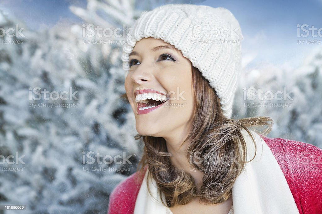 Beautiful woman laughing outdoors as snowflakes fall on her face royalty-free stock photo