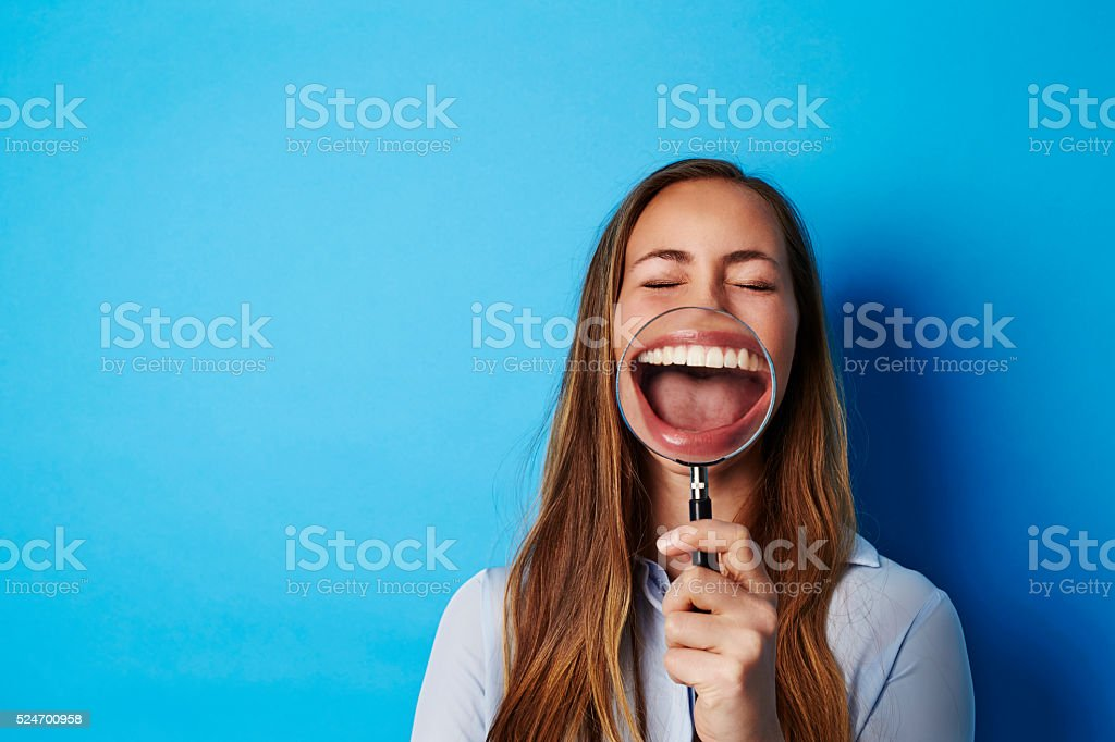 Beautiful woman laughing through magnifying glass stock photo