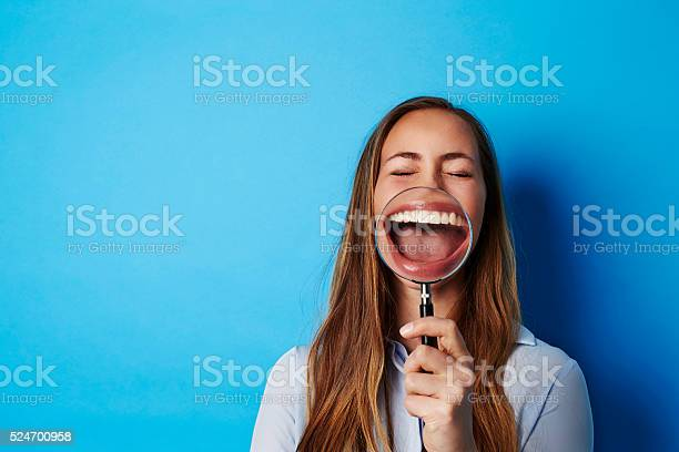 Beautiful Woman Laughing Through Magnifying Glass Stock Photo - Download Image Now