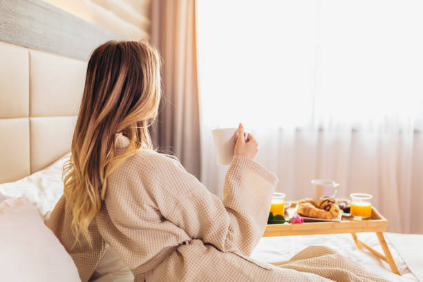 beautiful woman laying and enjoying, breakfast in bed - - accappatoio foto e immagini stock