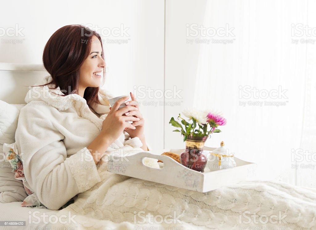 Beautiful woman laying and enjoying, breakfast in bed stock photo