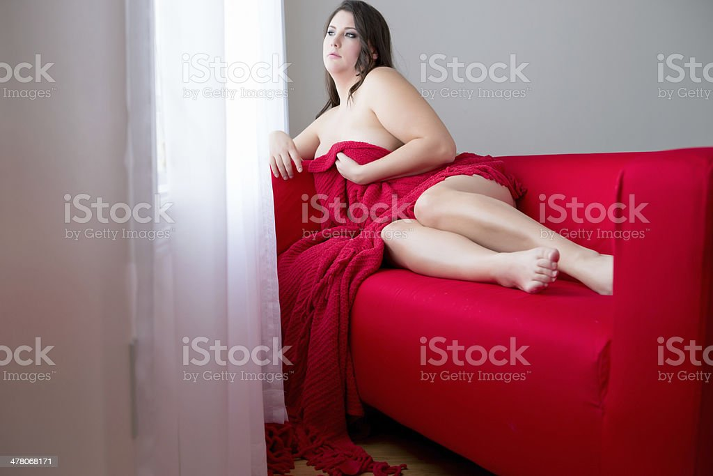 Beautiful woman laying on red couch royalty-free stock photo